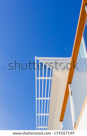 White aluminum louvers, modern style villa, against natural teak wood handrail with blue sky background