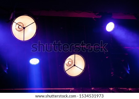 white an blue lights with floodlights enlightening a concert stage #1534531973