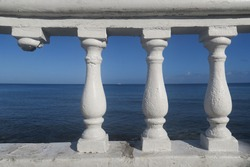 White ancient romantic style balustrade, one pillar is missing, the handrail is at the blue oceana and gives with a blue clear sky a perfect line with the horizont