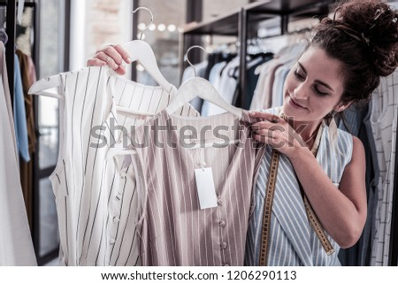 White and beige. Dark-haired fashion designer choosing between white and dark beige striped summer dress #1206290113