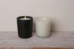 White and black candles. Two burning candles on wooden table against white wall.