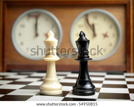 White and black king on the chessboard opposing each other,old chess clock in the background,can be used as concept for conflict,meeting,agreement..