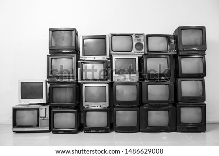 White and black, many retro old TVs piled together on the floor in the room. Television wall