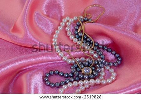 White and black pearl necklaces with diamond necklace on pink cloth background. #2519826