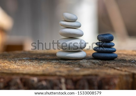 White and black stones cairns in daylight, poise light pebbles on wooden stump in front of brown natural background, zen like sculpture, simplicity, harmony and balance