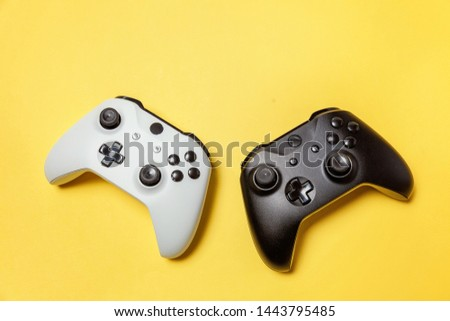 White and black two joystick gamepad, game console on yellow colourful trendy modern fashion pin-up background. Computer gaming competition videogame control confrontation concept. Cyberspace symbol