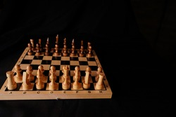 White and black wooden pieces on a chessboard. A chessboard set up during a game on a black background.