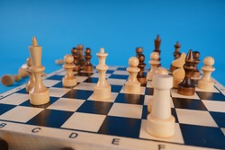 White and black wooden pieces on a chessboard. A chessboard set up during a game on a blue background