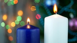 White and blue candles are burning over holiday bokeh blinking background and Christmas tree