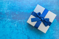 White and blue gift box with blue ribbon on blue background, top view. Gifts, celebration, valentines theme