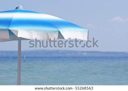 white and blue striped beach umbrella at Garda lake (Italy)