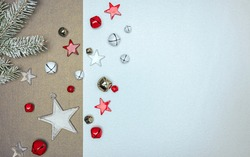 white and bronze background decorated with frosty christmas tree branch, glass stars and jingle bells