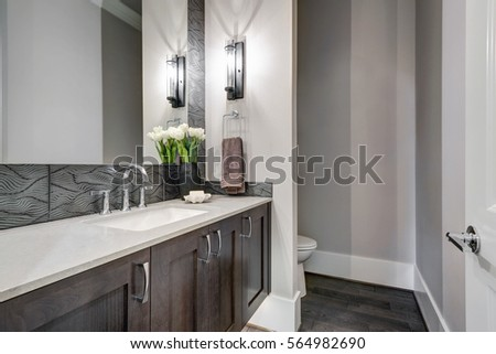 White and brown bathroom boasts a nook filled with a taupe vanity cabinet topped with white counter paired with wavy tile backsplash under a mirror lit by sconces. Northwest, USA