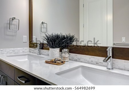 White and brown bathroom boasts a nook filled with double vanity cabinet topped with white and grey counter paired with tile backsplash under framed mirror. Northwest, USA Northwest, USA