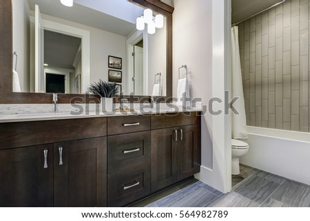 White and brown bathroom boasts a nook filled with double vanity cabinet topped with white counter paired with white and grey tile backsplash under a framed mirror lit by sconces. Northwest, USA