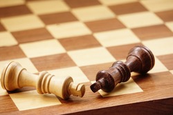 white and brown king fall on a wodden chess board.