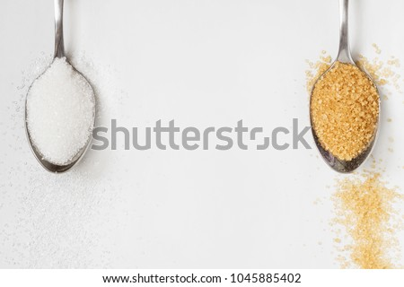 White and brown sugar in metal spoons on the light background with copy space. Top view, closeup, selective focus.