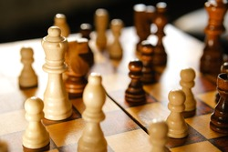 White and brown wooden chess pieces on board game.