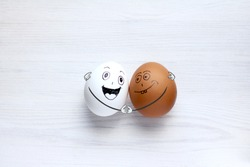white and colored eggs fun hugging each other. International Friendship Day