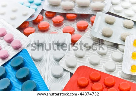 white and colored pills in blisters background