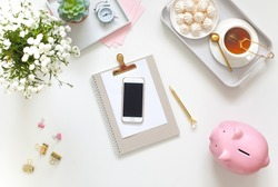 White and gold stationery at the female workplace. Jewelry, bracelets and rings. Alarm clock and pig piggy bank. Scandinavian nordic style. Stylized women's desk, office desk.