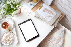 White and gold stationery at the female workplace. Jewelry, bracelets and rings. Flowers in a vase, tea and bizet. Alarm clock and pig piggy bank. Stylized women's desk, office desk.