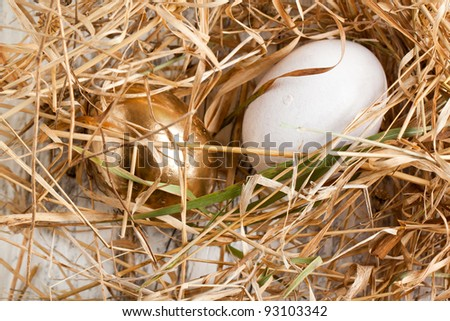 White and golden easter eggs in nest