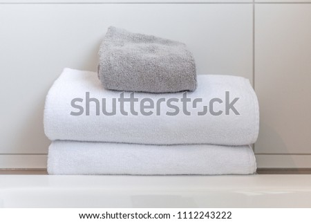 White and gray folded towels against white tiles in bathroom #1112243222