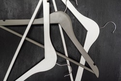 White and gray wooden hangers are chaotic lying on gray background. Top view