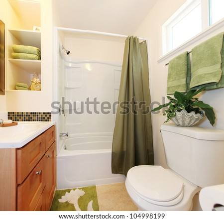 White and green bathroom with tub and wood cabinet.