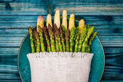 White and green fresh asparagus in linen fabric on blue plate on blue wooden table, close up. Different varieties of German green and white asparagus on the table.