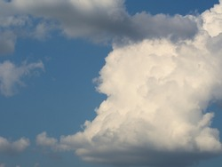 White and grey cloud in the blue summer sky .The cloud - Cumulonimbus - with the typical shape of an anvil - heralds a storm.