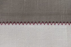 white and grey fabric stitched with a zigzag purple thread. Stitched pieces of fabric close-up. zigzag stitch.