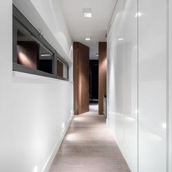 White and luxury home corridor with wardrobes, small window, wooden floor and door