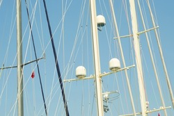 White and metal yacht masts with communications sensors and navigation devices against the blue sky and the Turkish flag