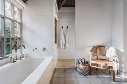 White and modern bathroom interior with chair, plaid, towels on hook and in basket, cute decor toys on built tub, large window in wooden frame with tropical foliage plants and copy space on wall