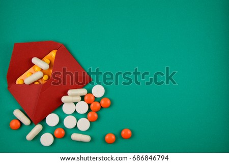 white and orange pills in red envelope on green background #686846794