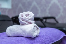 White and purple clean Many cotton towels pile on armchairs in bathroom shelf in spa salon for washing hair and taking care of hair salon in beauty salon