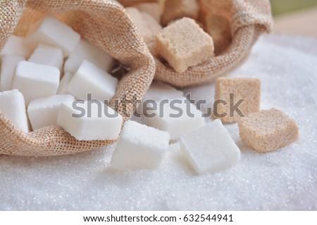 White and raw cube sugar  on white granulated sugar