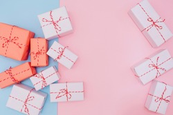 white and red boxes with gifts tied with ribbon on a pink and blue background, top view. Delicate background for New Year and Christmas, Valentine's Day, Mother's Day. Place for text.