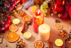 White and red burning candles on the table. Bright christmas decorations, warm colours cozy atmosphere, pleasant mood of the photo.