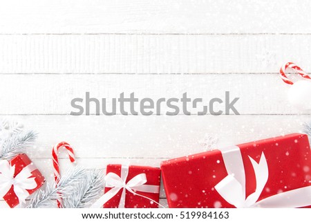 White and red Christmas theme background with gift boxes and decorating elements, top view on wood table, border design