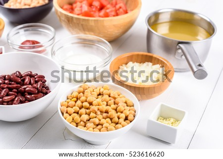 White And Red Kidney Beans, Ketchup, Tomatoes, Yogurt, Chickpeas, Garlic, Onion And Vegetable Stock Food Ingredients On White Wood Table