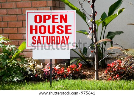 White and red open house sign in front of the small suburban house.