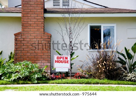 White and red open house sign in front of the small suburban house. There is some additional space for text on the sign.