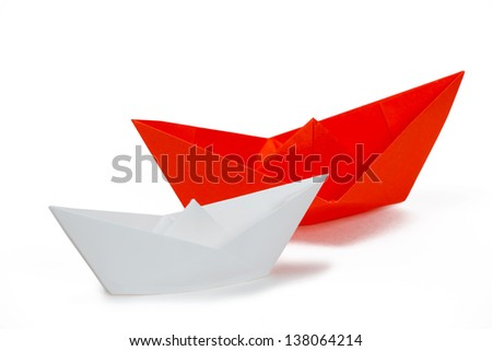 White and red paper ships on a white background