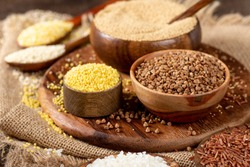 White and red rice, buckwheat, amaranth seeds, corn groats, quinoa and millet in bowls on a brown wooden table. Gluten-free cereals. Closeup
