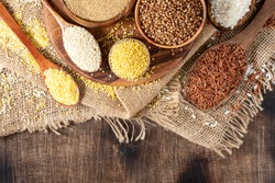 White and red rice, buckwheat, amaranth seeds, corn groats, quinoa and millet in bowls on a brown wooden table. Gluten-free cereals. Top view with copyspace