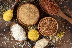 White and red rice, buckwheat, amaranth seeds, corn groats, quinoa and millet in bowls on a brown wooden table. Gluten-free cereals. Top view