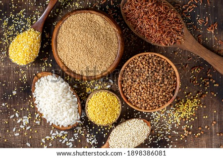 White and red rice, buckwheat, amaranth seeds, corn groats, quinoa and millet in bowls on a brown wooden table. Gluten-free cereals. Top view Stockfoto ©